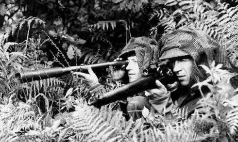 Снайперская пара с телескопом в джунглях.