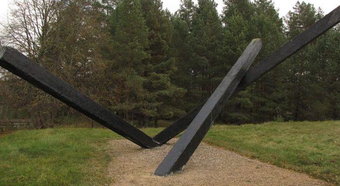 Три черные бетонные балки, символизирующие обугленные остатки дома.
