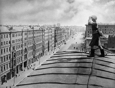 Боец ПВО ведет наблюдение с крыши дома на улице Горького. Осень, 1941 г.