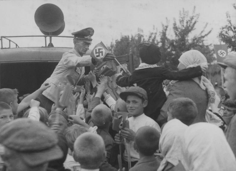 Сотрудник рейхсминистерства оккупированных восточных территорий раздает флажки со свастикой жителям Киева во время празднования второй годовщины захвата города немецкими войсками. 19 сентября 1943 г.