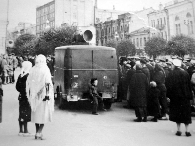 Жители Киева слушают сообщения о эвакуации населения через громкоговоритель, установленный на крыше автомобиля 637-й роты пропаганды вермахта, стоя на Крещатике. Сентябрь, 1941 г.