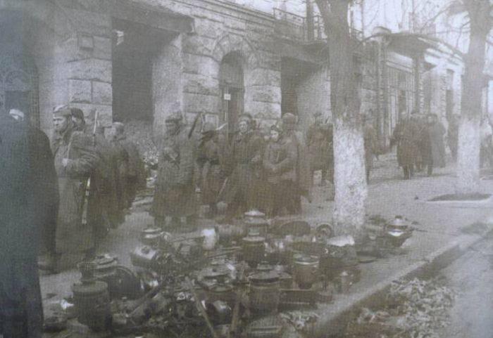 Советские солдаты идут по улице Киева. На тротуаре горы награбленных вещей, их не успели вывезти немцы. 6 ноября 1943 г.