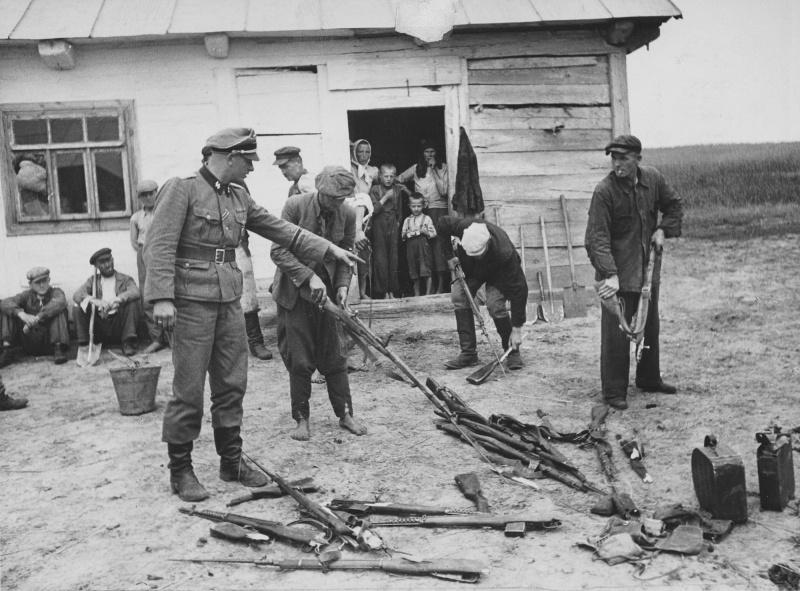 Жители деревни ломают собранные советские винтовки под контролем офицера СС.