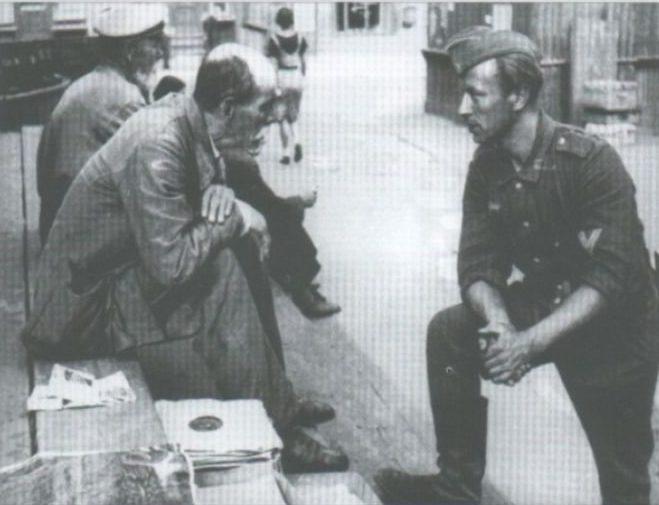 Торговец граммофонными пластинками беседует с немецким солдатом.