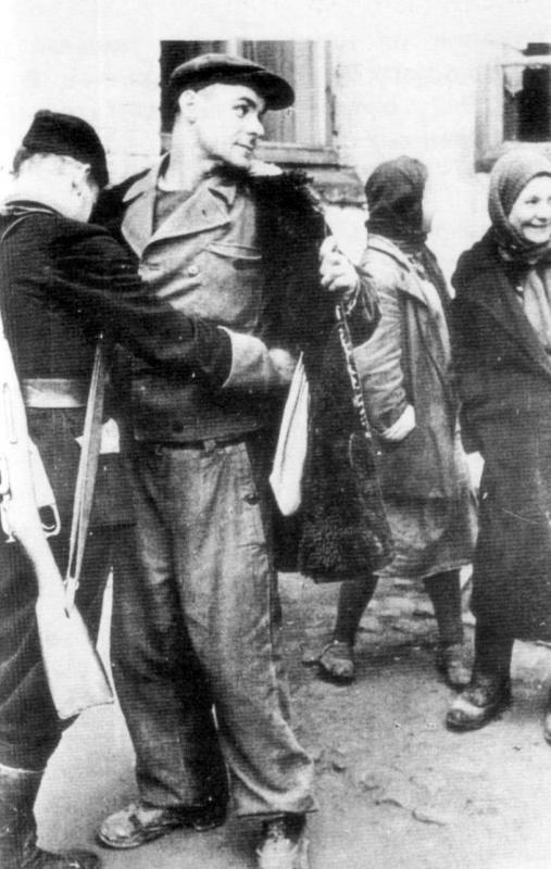 Обыск рабочего украинским полицейским на кондитерской фабрике в Киеве. Декабрь, 1942 г.