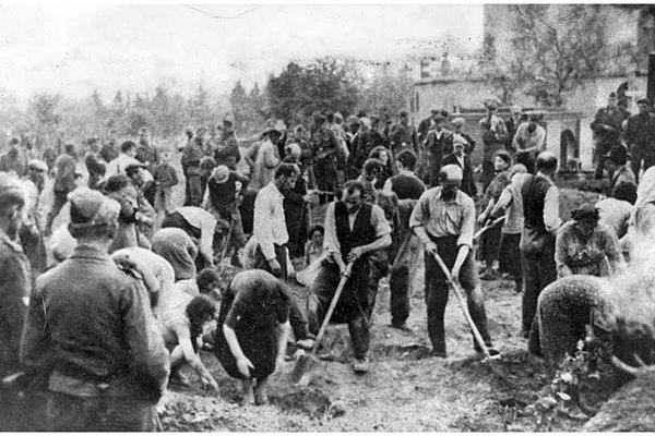 Советские военнопленные под конвоем эсэсовцев засыпают землей участок Бабьего Яра, где лежат расстрелянные. 1 октября 1941 г.
