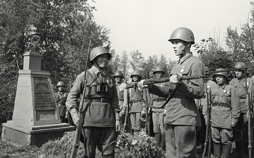 Снайпер С. Номоконов вручает молодому бойцу Б.Канатову винтовку погибшего снайпера.