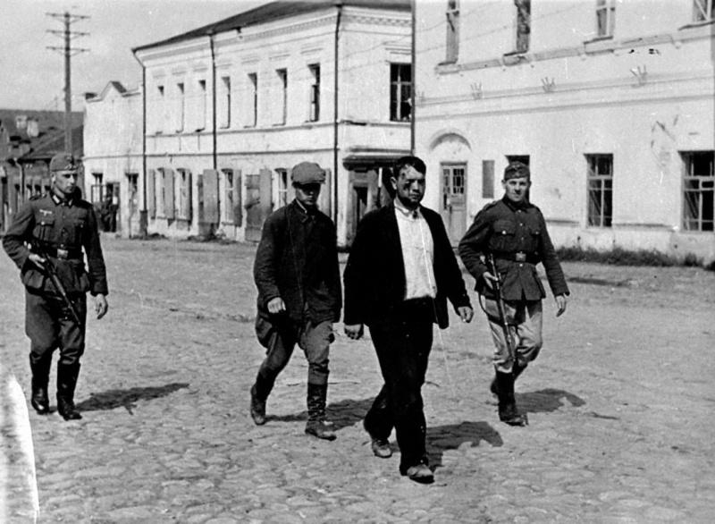 Немецкий патруль ведет пойманных переодетых советских солдат. Сентябрь, 1941 г.