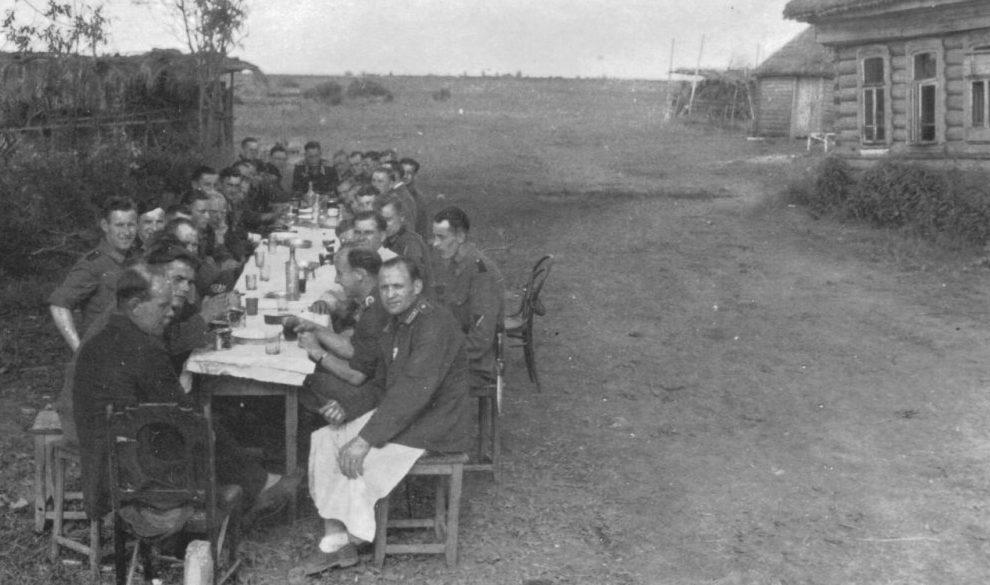 Немецкие солдаты за столом на улице оккупированной советской деревни.