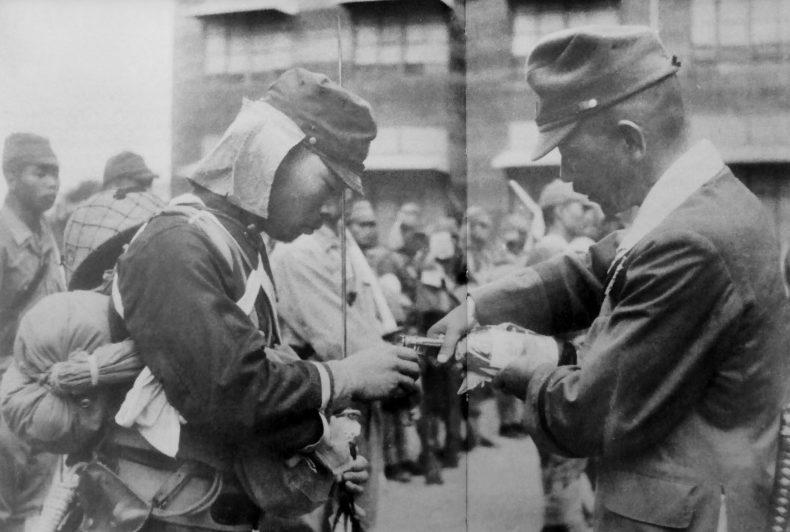 Киодзи Томинага наливает саке командиру спецгруппы лейтенанту Шигео Нака перед вылетом на операцию. Манила, Филиппины, 26.11.1944 г.