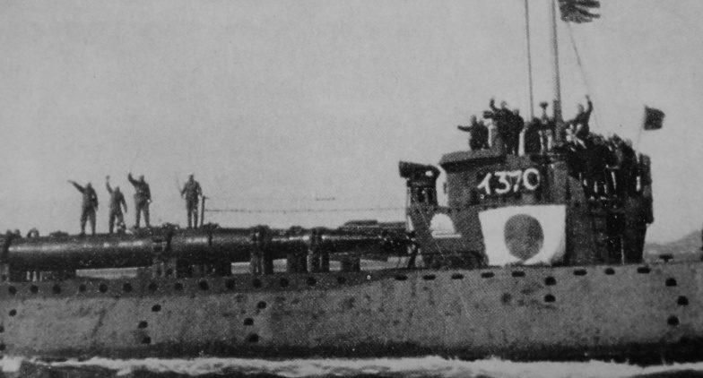 Японская подводная лодка I-37 выходит в боевой поход с человекоуправляемыми торпедами «Кейтэн», на которых (cлева) стоят пилоты-смертники с мечами и с повязками на головах. 1945 г.