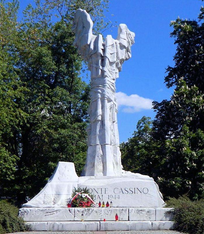 г. Варшава. Памятник в честь битвы при Монте-Кассино расположен на площади между улицами Андерс и Сада Красинских. Он был открыт в 1999 году в память солдат 2-го Польского Корпуса, которые в 1944 году после ожесточённых боёв, продолжавшихся в течение несколько недель в районе горы Монте-Кассино в центре Италии, захватили монастырь, который немцы использовали как крепость. Это позволило открыть союзникам дорогу на Рим. Монумент изготовлен из железобетона и покрыт белым мрамором. Это 12-метровая колонна в виде обезглавленной древнегреческой богини Ники, которая считается богиней победы. При взгляде на колонну, кажется, будто она истерзана и изранена в бою. Рядом на двухметровом цоколе стоит урна с прахом погибших героев, на которой виден крест Монте-Кассино и высечены гербы пяти польских подразделений, принимавших участие в битве. Известно, что в той битве было убито 924 бойца, а 4 199 - были ранены.