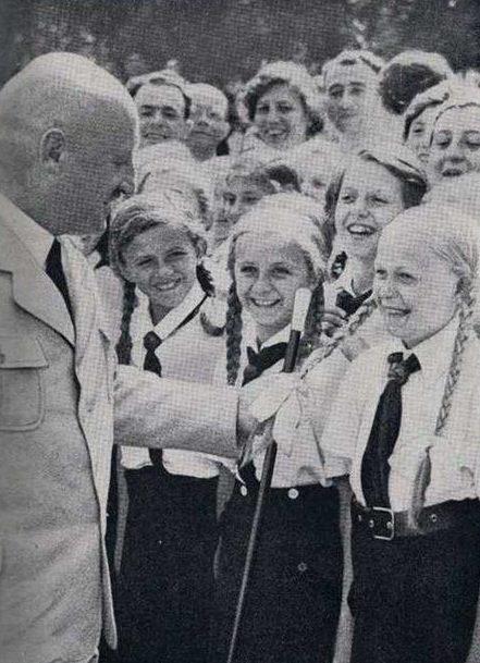 Юлиус Штрайхер, «расовый теоретик» партии, одобряет светлые косы девушки.
