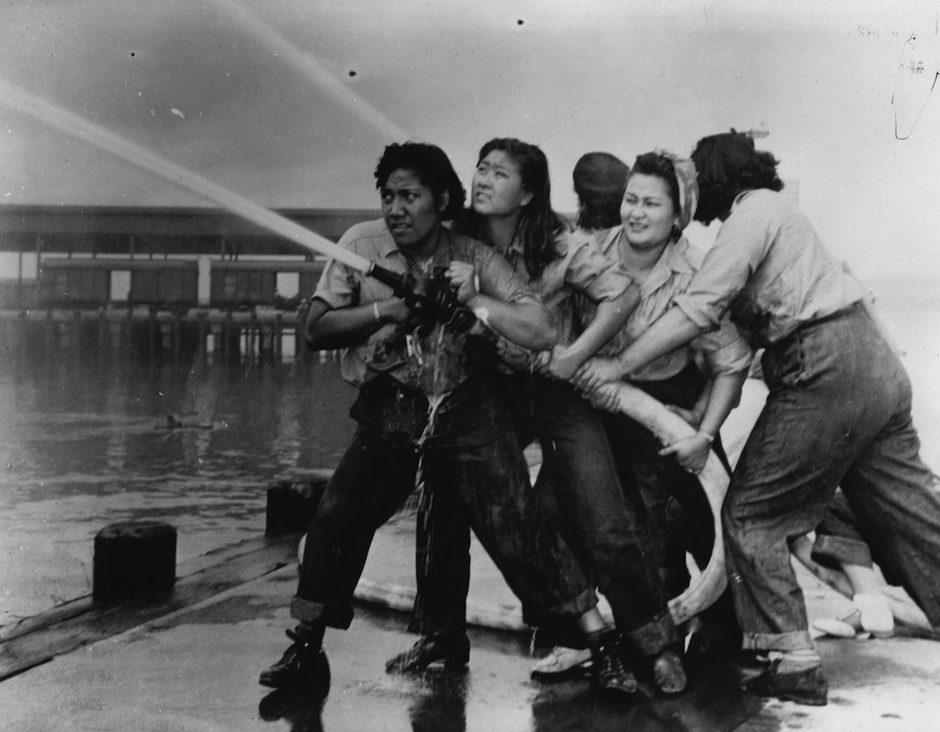 Женщины-пожарные пытаются погасить пожар после нападения на Перл-Харбор. 7 декабря 1941 г.