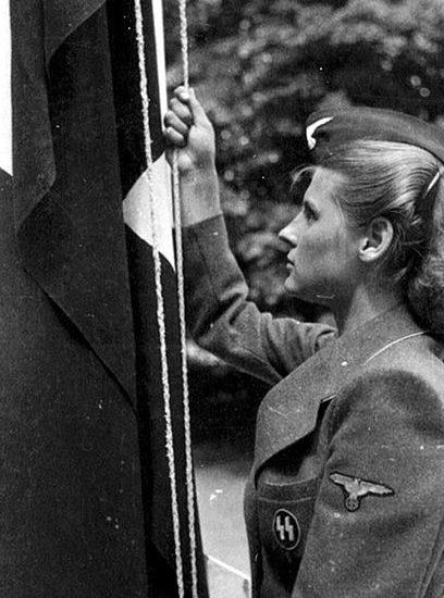 Служащая вспомогательной службы СС поднимает флаг.