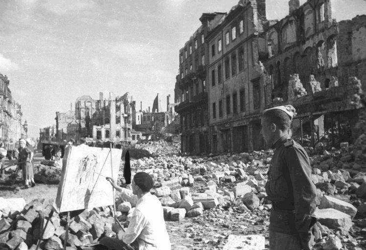 Советский солдат наблюдает за работой немецкого художника. 1945 г.