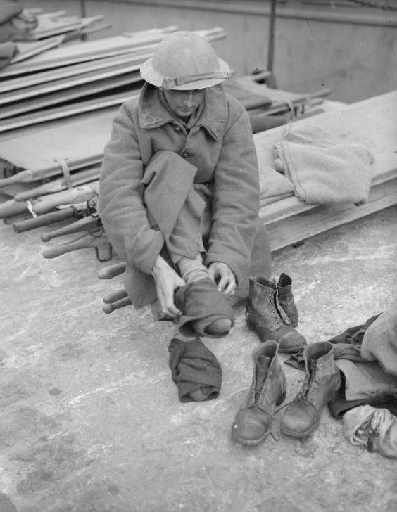 Эвакуированный солдат, одетый во французское пальто, меняет свои носки и ботинки. Довер, 31 мая 1941 г.
