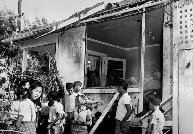 Люди осматривают повреждения дома после авианалета. 7 декабря 1941 г.
