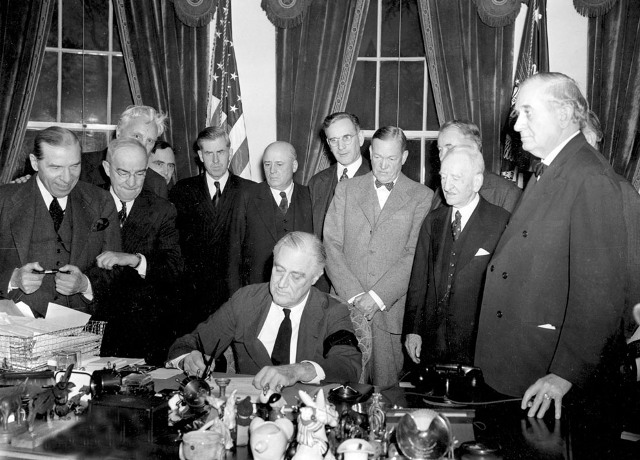 Президент США Франклин Рузвельт после атаки японцев на Перл-Харбор подписывает декларацию об объявлении войны Японии. 8 декабря 1941 г.