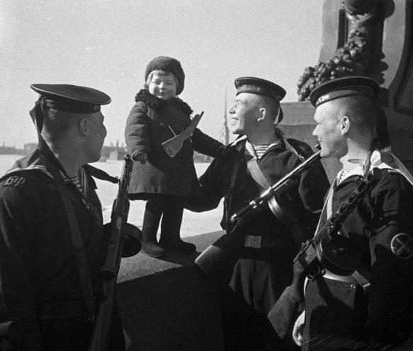 Моряки Балтийского флота с маленькой девочкой Люсей, родители которой умерли в блокаду. Ленинград, 1 мая 1943 г.
