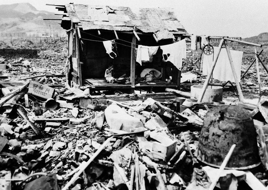 Японская семья ест рис в шалаше, построенном из обломков, оставшихся на том месте, где когда-то находился их дом в Нагасаки. 14 сентября 1945 г.