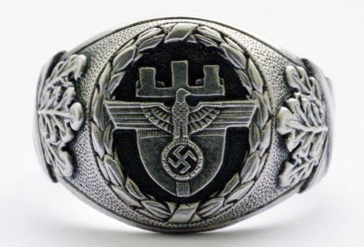 Перстень за основу дизайна щитка, которого взят знак НСДАП Гау Восточная Пруссия. Кольцо выполнено из серебра 835-ой пробы с применением чернения.