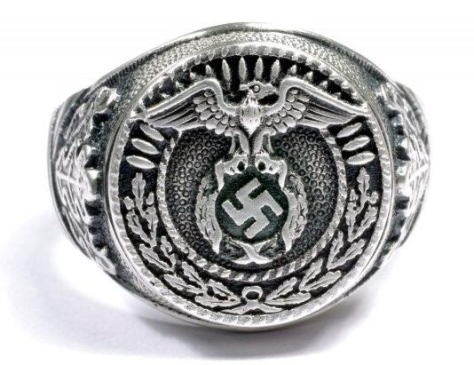 Перстень члена НСДАП выполнен из серебра 835 пробы с применением чернения. По бокам щитка нанесен рельефный растительный орнамент.