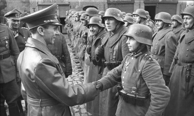 Йозеф Геббельс поздравляет 16-летнего солдата Вильгельма Хюбнера после награждения его Железным крестом 2 класса. Любань. 1945 г.