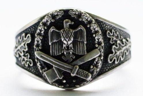 Наградной перстень выполнен из серебра 835-ой пробы с чернением. За основу дизайна щитка взят нагрудный знака Вермахта «За штурмовую атаку». По обоим бокам от щитка, кольцо украшено рельефным растительным орнаментом.
