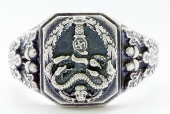 Наградные перстни из серебра 800-ой пробы с чернением. Дизайн щитка кольца напоминает нагрудный знак «За борьбу с партизанами». Как правило, перстнем награждались члены карательных отрядов.