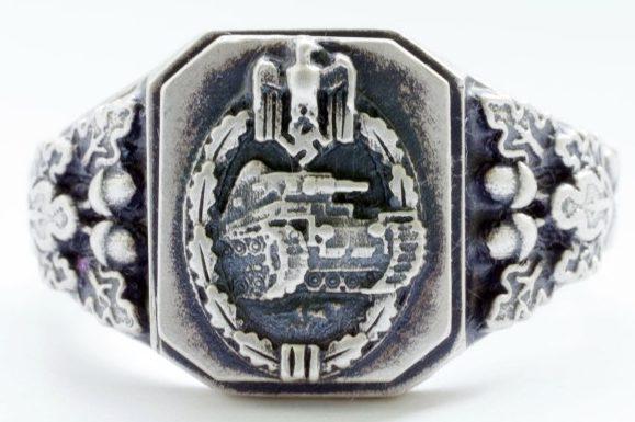 Наградной перстень с изображением элементов нагрудного знака «За танковые атаки» изготавливался из серебра 835-ой пробы с применением чернения. Знак наложен на традиционный рельеф из дубовых листьев.