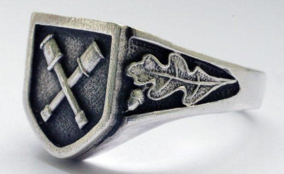 На щитке перстня рельефное изображение символа 36-й дивизии СС «Дирливангер». По сторонам щитка - орнамент из дубовых листьев. Кольцо изготовлено из серебра 830-ой пробы с применением чернения.
