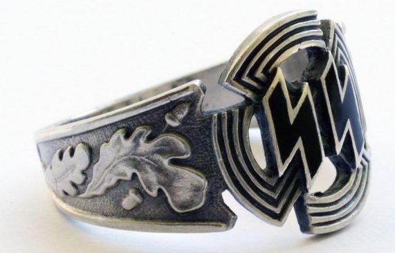 За основу дизайна щитка перстня взята эмблема «Спортивного знака CC». По сторонам щитка наложен традиционный орнамент из дубовых листьев. Кольцо изготовлено из серебра 830-ой пробы с применением чернения.