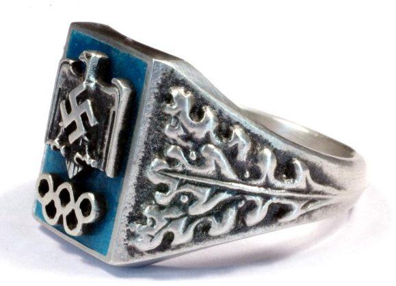 Перстень посвящен олимпийским играм, прошедшим в Германии в 1936 г. Он изготовлен из серебра 800-ой пробы с применением горячей цветной эмали.