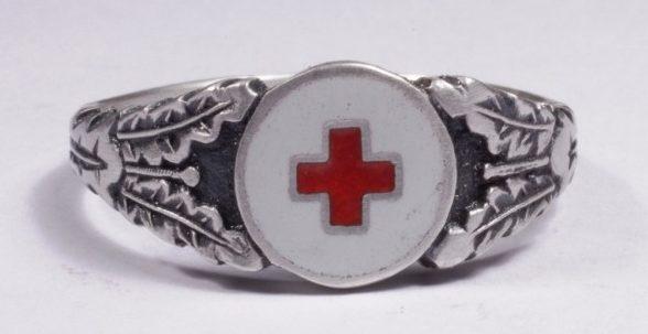 Кольцо служащих Германского Красного Креста изготовленное из серебра 830-й пробы с применением чернения и цветной горячей эмали. По сторонам от щитка расположен традиционный растительный орнамент из дубовых листьев.