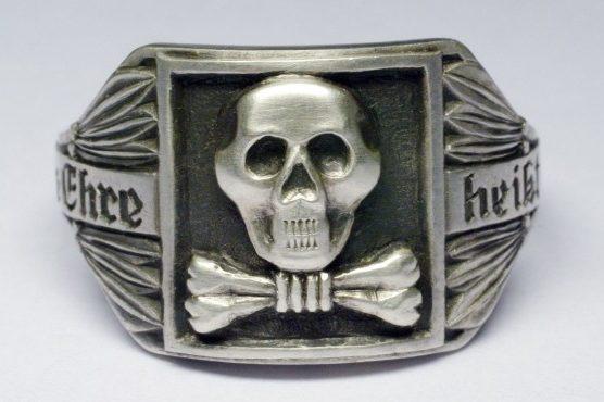 Перстень с черепом «мертвая голова» и костями изготовлен из серебра 835-й пробы с применением чернения. По сторонам щитка наложен орнамент из лавровых листьев и размещена надпись «Meine Ehre heißt Treue» (Верность - моя честь).