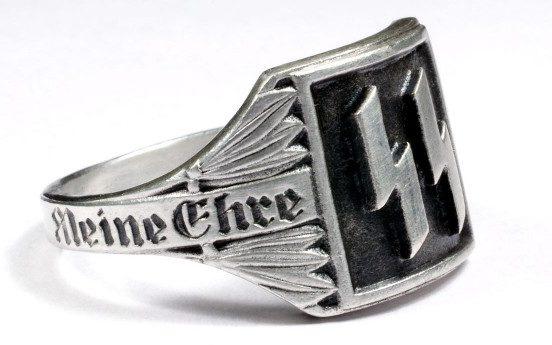 Перстень с двойной руной «Зиг» изготовлен из серебра 835-й пробы с применением чернения. По сторонам щитка наложен орнамент из лавровых листьев и размещена надпись «Meine Ehre heißt Treue» (Верность - моя честь).
