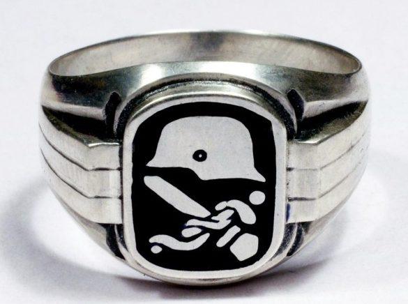 Кольцо персонала Германского медицинского корпуса изготовлено из серебра 835-й пробы. Эмблема медицинского корпуса выполнена из белой и черной горячей эмали.