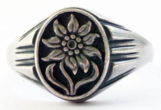 Наградной перстень с изображением эдельвейса изготовлен из серебра 835-ой пробы с применением чернения. Поля щитка На щитке - рельефное изображение эдельвейса. Использовался в качестве дивизионной награды в горнострелковых частях.
