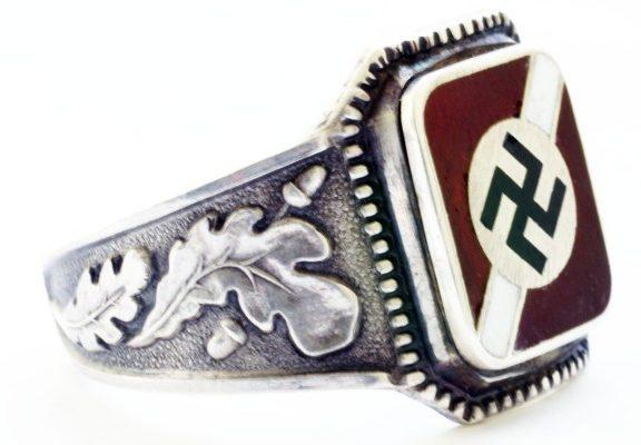 Перстень Латышского добровольческого легиона СС изготовлен из серебра 900-ой пробы с использованием цветной горячей эмали. По сторонам щитка наложен традиционный орнамент из дубовых листьев.