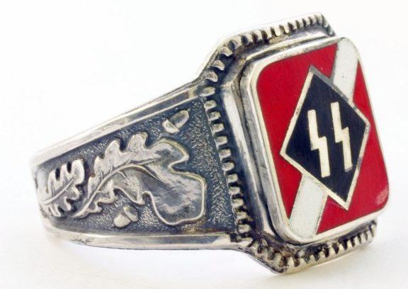 Перстень Латышского добровольческого легиона СС изготовлен из серебра 900-ой пробы с использованием цветной горячей эмали. На щитке изображена двойная руна «Зиг» на фоне цветов Имперского флага. По сторонам щитка наложен традиционный орнамент из дубовых листьев.
