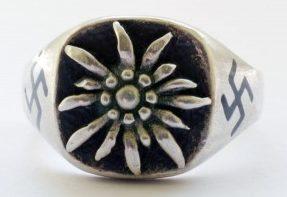 Перстень из серебра 835-ой пробы с рельефным изображением эдельвейса. С обеих сторон щитка вытравлена свастика. Поле щитка зачернено.