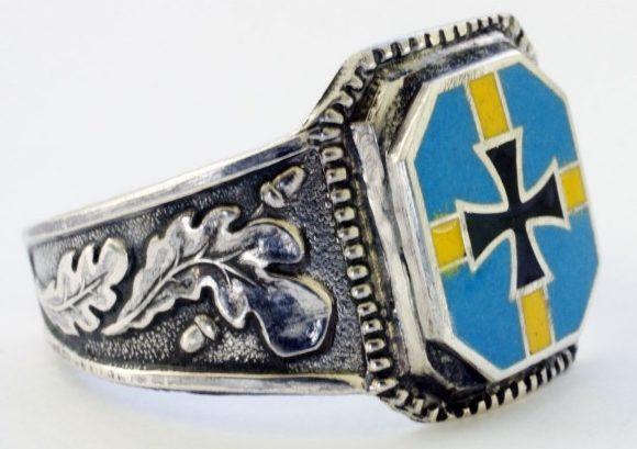 Перстень шведского солдата добровольческого легиона СС изготовлен из серебра 900-ой пробы с использованием чернения и цветной горячей эмали. В основу дизайна щитка взят Шведский флаг времен Третьего Рейха. По сторонам щитков наложен традиционный орнамент из дубовых листьев.