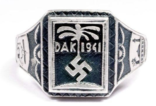 Перстень «Немецкий Африканский Корпус 1941» изготовленный из серебра 835-ой пробы с применением чернения. На его щитке изображена эмблема корпуса – свастика на фоне пальмы, а также надпись «DAK 1941».