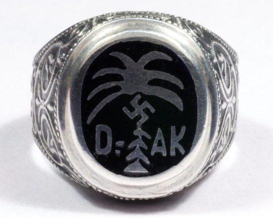Перстень «Немецкий Африканский Корпус» изготовленный из серебра 835-ой пробы с применением горячей черной эмали. На щитке изображена эмблема корпуса – свастика на фоне пальмы.