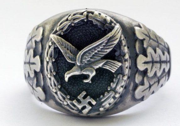 Наградное кольцо летчика-наблюдателя, выполнено из серебра 835-ой пробы. По сторонам от щитка расположен традиционный орнамент из дубовых листьев. Поле щитка обработано чернением.