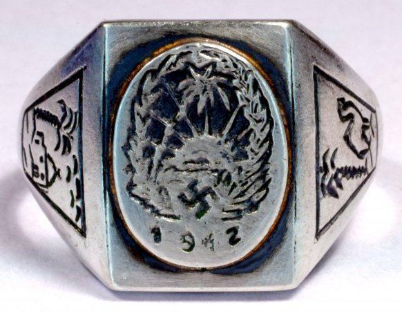 Памятный перстень «Немецкий Африканский Корпус 1942» изготовленный из серебра 835-ой пробы. На щитке изображена эмблема корпуса – свастика на фоне пальмы и восходящего солнца. По обеих сторонах щитка изображена пальма.