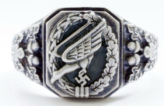 Перстень парашютиста Люфтваффе, выполненный из серебра 835-ой пробы. По сторонам от щитка расположен орнамент из желудей и дубовых листьев. Поле щитка обработано чернением.