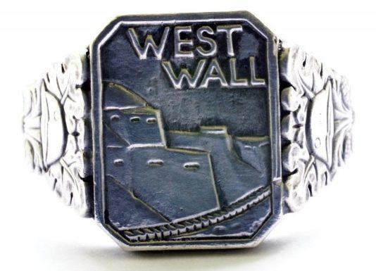 Памятные перстни с надписью «West Wall» (Западный вал) выполнены из серебра 835-ой пробы с применением чернения. По сторонам от щитка расположен растительный орнамент в виде дубовых листьев. Перстни вручались участникам строительства и защитникам Западного вала.