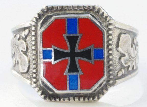 Перстень, за основу дизайна щитка которого, взят норвежский флаг времен Третьего Рейха, изготовлен из серебра 900-ой пробы. По сторонам щитка наложен традиционный орнамент из дубовых листьев. При изготовлении применена цветная горячая эмаль.
